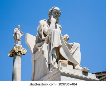 Academy of Athens, Athens, Greece, June 4 2008: White marble statue of Socrates with Apollo in background against a vivid blue sky