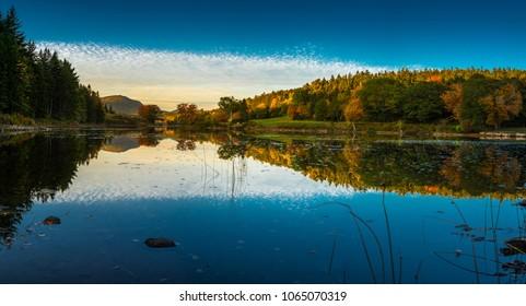 Acadia National Park during peak fall foliage season reflecting in the lake.