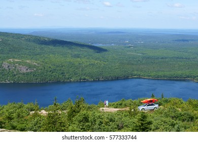Acadia National Park in U.S. state of Maine. Tourists with car and canoe watching panorama from summit of Cadillac Mountain