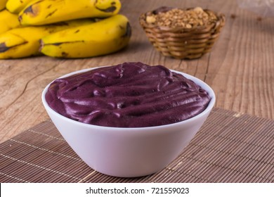 Acai with banana and granola over a wooden table