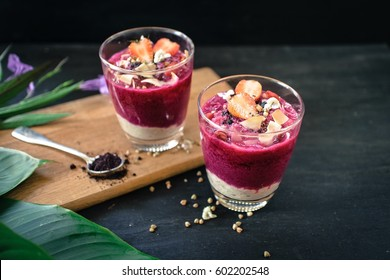 acai berry smoothie topped with strawberry, coconut flakes , buckwheat and goji berries.