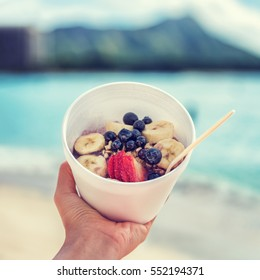 Acai bowl food selfie picture. Closeup of healthy breakfast take-out on ocean background at hawaii beach. Berries and fresh fruits outdoors for a weight loss diet. Square crop for social media.