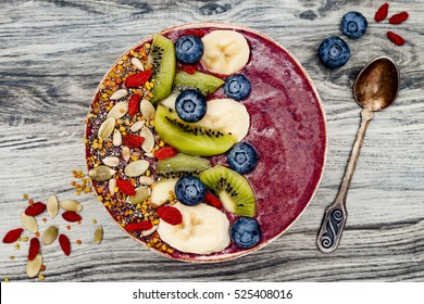 Acai breakfast superfoods smoothies bowl with chia seeds, bee pollen, goji berry toppings and fruits. Overhead, top view, flat lay.