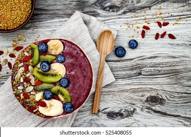 Acai breakfast superfoods smoothies bowl with chia seeds, bee pollen, goji berry toppings and fruits. Overhead, top view, flat lay, copy space.