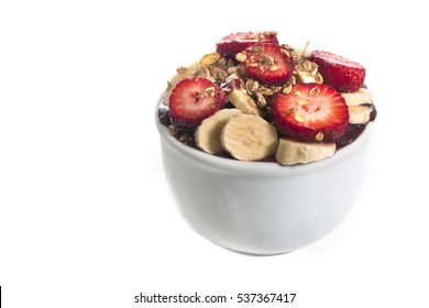 Acai cream with banana and strawberry in bowl isolated over white background. Brazilian famous fruit from Amazon.