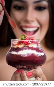 Acai served in fancy glass with model out of focus as background
