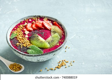 Acai smoothie bowl with chia seeds, fruits, berries (strawberries) and bee pollen for healthy vegan vegetarian diet raw breakfast. Breakfast smoothie bowl on white background, copy space.
