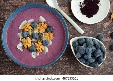 Acai smoothie bowl topping with walnut, coconut chips and blueberries