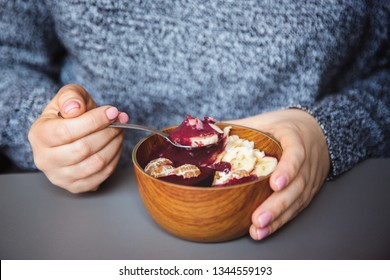 Acai smoothie, granola, seeds, fresh fruits in a wooden bowl in female hands on grey table. Eating healthy breakfast bowl