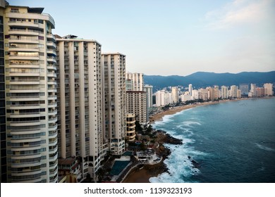 Acapulco bay with its characteristic line of hotels in front of a tiny beach line with a beautiful blue ocean on a sunny summer day