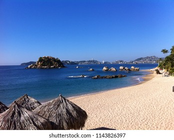 Acapulco beach's dark blue water with rocks islands and warm sand under a totally clear sky and palapas on the edge