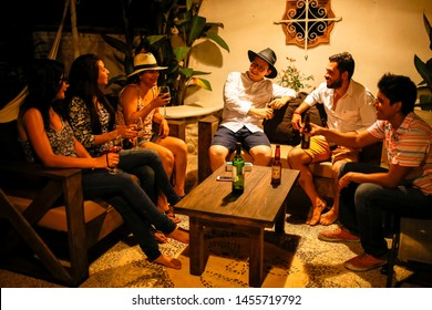 Acapulco, Guerrero / Mexico - June 15 2016: A group of friends hag around and drink beer and wine while they talk deep into the night