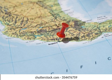 Acapulco marked on map with red pushpin. Selective focus on the word Acapulco and the pushpin. Pin is in an angle and casts some shadow to the right.