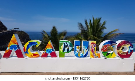Acapulco, Mexico - April 9, 2019: Beautiful colorful Acapulco inscription sign with bright colorful letters and blue ocean and trees as background