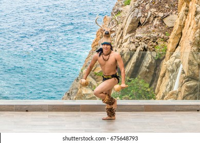 ACAPULCO, MEXICO - June 11, 2017: Dancer with a deer headdress performs on a stage high above the Pacific Ocean to demonstrate Aztec and Mexican dance and culture to tourists in Acapulco, Mexico.