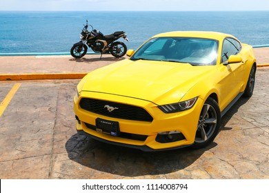 Acapulco, Mexico - May 31, 2017: Yellow muscle car Ford Mustang and naked bike Yamaha FZ25 in the city street at the background of the Pacific Ocean.