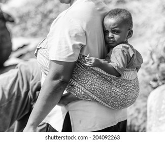 ACCARA, GHANA - MAR 2, 2012: Unidentified Ghanaian woman carries her little baby on her back in black and white. People of Ghana suffer of poverty due to the unstable economical situation
