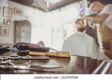 Accesories for cutting on the table in a barbershop and a hairdresser works in the background.  Photo in vintage style