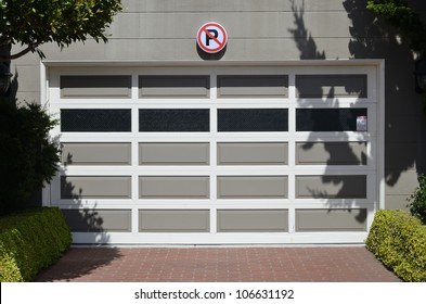 Access to a garage with a no parking sign displayed above the door