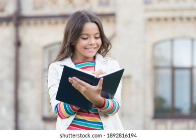 Access to much more than just book. Knowledge concept. Little girl hold book. Girl with book school building background. Book from library. Making notes. Inspired poet. Talented cute schoolgirl.