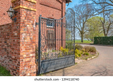 Access to an old farm. The facade and the walls of the enclosure are made of brick. In the foreground you can see an open wrought-iron gate.