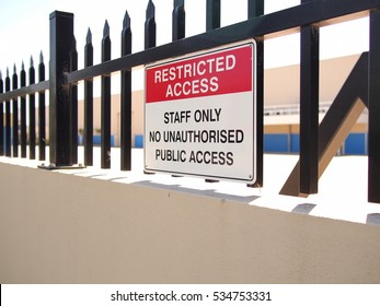 Access restricted sign on a steel fence tipped wall of an industrial estate, Melbourne, Australia 2016