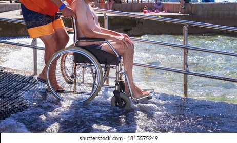 Accessible beach with ramp for disabled people. Man on wheelchair going swimming.