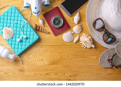 Accessories for a bright summer Sunny holiday in the resort. Items for travel to the sea laid out on a wooden table. Top view. Flat lay