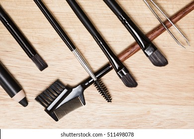 Accessories for care of brows and lashes: brow comb / brush combo, spoolie brush, angled brushes, eyebrow pencil, tweezers on wood background. Eyebrow and eyelashes grooming tools