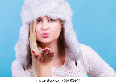 Accessories and clothes for cold days, fashion concept. Blonde woman in winter warm furry hat in russian style making air kisses.