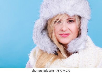Accessories and clothes for cold days, fashion concept. Blonde woman in winter warm furry hat in russian style and scarf.