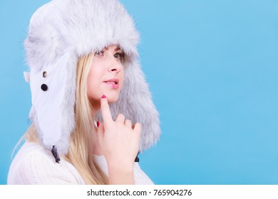 Accessories and clothes for cold days, fashion concept. Blonde woman in winter warm furry hat in russian style.