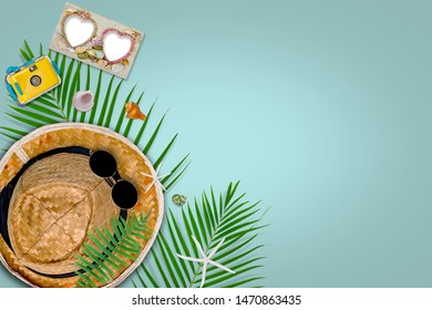 accessories composition for summer concept with tropical palm leaves on pastel blue background, top view and copy space