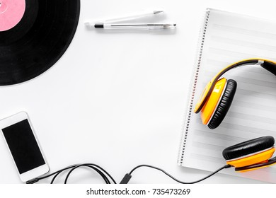 Accessories of contemporary composer. Headphones. phone, vinyl record, music notes on white background top view copyspace