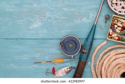 Accessories for fishing on the background of wood. Background of blue color. Several float, hook, sinker, rod for ice fishing, a coil of rope. Bait for fishing.