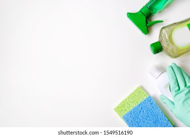 Сleaning accessories. Flat lay of green and white cleaning supplies on white background. Detergents in plastic bottles. Top view. Close up.