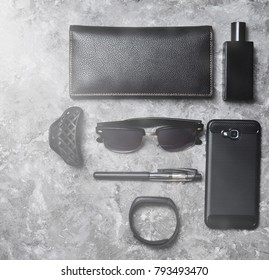 Accessories and gadgets for a business woman on a concrete surface. Smartphone, smart bracelet, pen, perfume bottle, purse, sunglasses. Top view. Space for text.