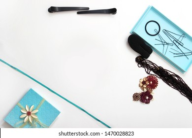 Accessories and hair pins flat lay. Sponge for hair, hairdo babette. necklaces of beads or flowers, tiffany blue boxes made of cardboard. turquoise ribbon. White background with copy space for text.