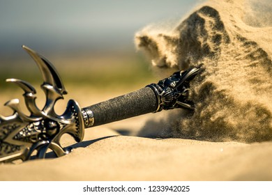 Accessories of a knight isolated on the sand during the day. Conceptual image. Sand is spreading.