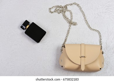 Accessories in modern style on white or grey texture background. Purse in light beige color with chain and perfume. Handbag for women and black bottle of scent, top view. Fashion and style concept