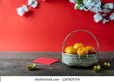 Accessories on Lunar New Year & Chinese New Year vacation concept background.Orange in wood basket with  red pocket money and flower on modern rustic brown & red backdrop at home office desk studio.