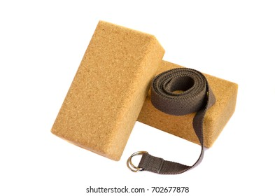 Accessories for practicing yoga or pilates. Two cork blocks and grey strap on white background. Isolated image. Active lifestyle, sport concept.
