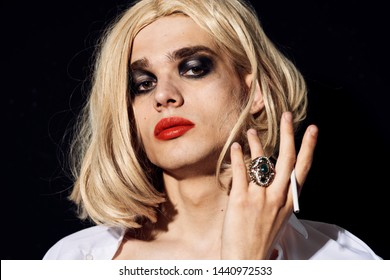 accessories ring man in a wig with makeup on a black background portrait of a drag queen