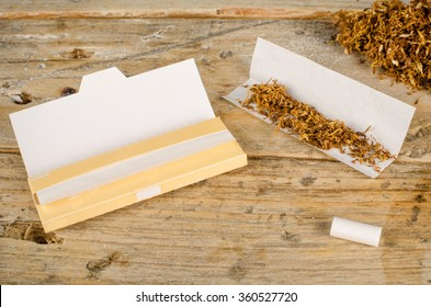 Accessories for rolling and smoking cigarettes on a rustic wooden table