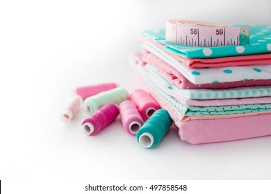 Accessories for sewing lie on a white background. Measuring tape, thread, fabric and needles for sewing. Fabric pink, mint, and turquoise.