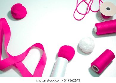 Accessories for sewing lie on a white background. Measuring tape, thread, fabric and needles .