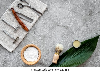 Accessories for shaving. Shaving brush, razor, foam, sciccors on grey stone table background top view copyspace