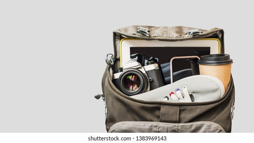 Accessories for travel. Camera, smartphone and other objects in the backpack over gray background. Holidays, traveling and tourism concept
