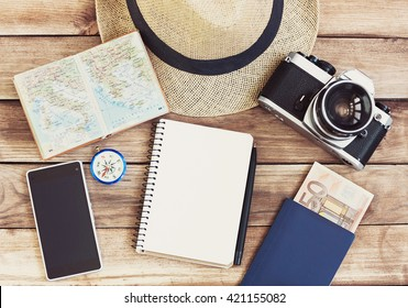 Accessories for travel. Passport, photo camera, smart phone and travel map. Top view. Holidays and tourism concept