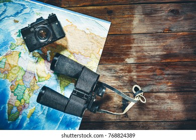 Accessories for travel Vintage Film Camera, Map And Binoculars On Wooden Table, Top View. Adventure Travel Scout Journey Concept